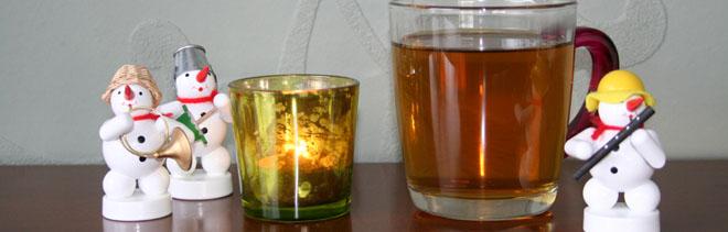 Ein Glas Tee, eine Kerze und drei kleine Schneemänner aus Holz